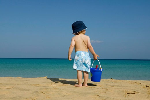 Stock Photo: 1669R-9369 rear view of toddler standing on beach holding bucket