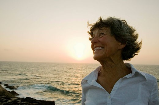 Stock Photo: 1669R-9462 portrait of smiling mature woman on beach at sunset