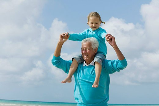 portrait of grandfather carrying young girl piggyback : Stock Photo