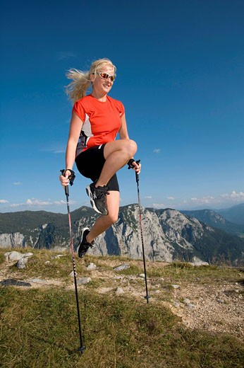 young woman in nordic walking outfit jumping over ski poles : Stock Photo