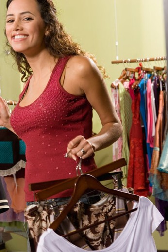 Portrait of a young woman holding dresses in a clothing store and smiling : Stock Photo