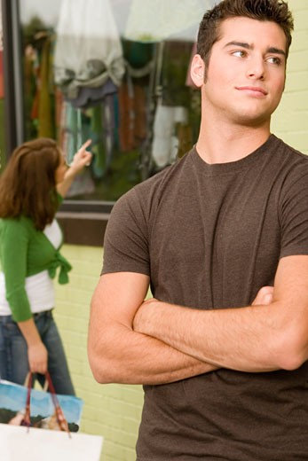 Stock Photo: 1670-105 Close-up of a teenage boy looking sideways with a young woman shopping behind him