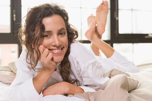 Portrait of a young woman lying on the bed and smiling : Stock Photo