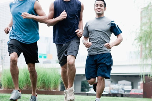 Close-up of three young men jogging : Stock Photo