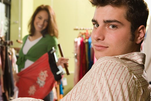 Portrait of a teenage boy in a garment store with a young woman shopping in the background : Stock Photo