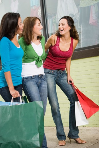 Three young women holding shopping bags and laughing : Stock Photo