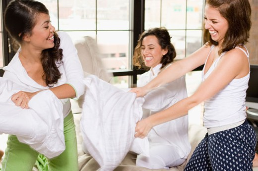 Three young women having a pillow fight on the bed : Stock Photo