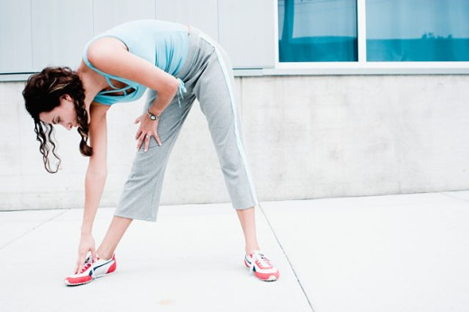 Young woman exercising on a sidewalk : Stock Photo