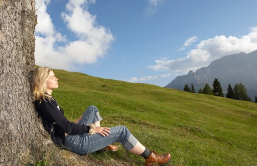 Italy, Alto Adige, young woman sitting against tree, eyes closed : Stock Photo