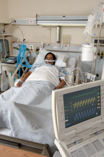 She is also hooked up to an IV, electrocardiogram monitor and there is an intra-aortic balloon pump reading on the monitor in the foreground. : Stock Photo