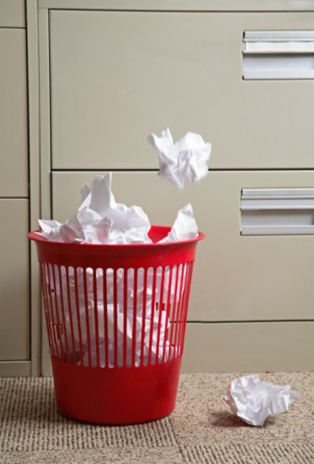 Crumpled paper falling into wastepaper basket : Stock Photo