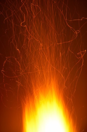 Blazing fire with emanating sparks, close-up : Stock Photo