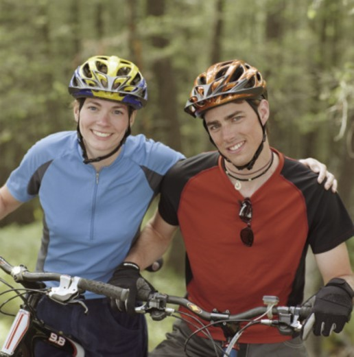 Young couple outdoors on bikes, smiling, portrait : Stock Photo