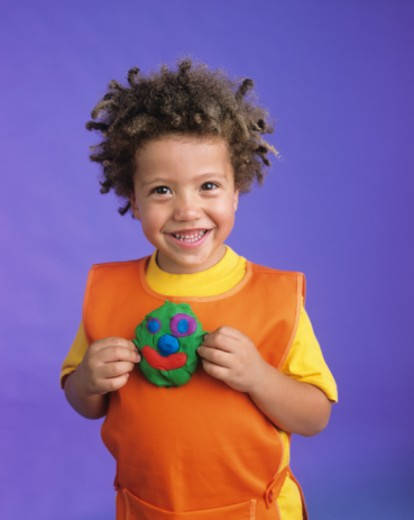 Stock Photo: 1672R-13176 Boy (4-6) holding face made of child's play clay, smiling, portrait