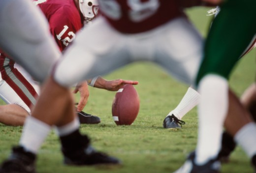 Stock Photo: 1672R-13297 USA, California, American football being kicked, view through legs