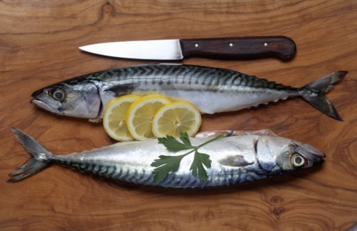 Stock Photo: 1672R-13614 Two fresh mackerel and knife on chopping board, close-up