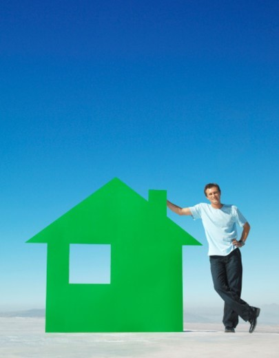 Stock Photo: 1672R-13656 Man leaning on model of green coloured house on roof top