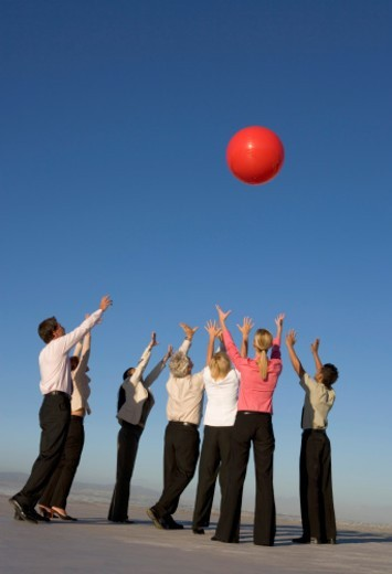 Group of business people reaching for red ball on roof : Stock Photo