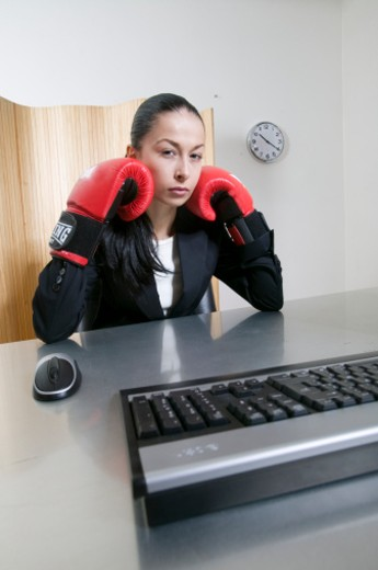 Stock Photo: 1672R-14000 Young woman sitting at desk in office, wearing boxing gloves