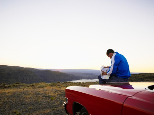 Stock Photo: 1672R-14131 Young man sitting on hood of car, reading map