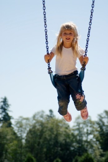 Stock Photo: 1672R-14189 Girl (4-5) on swing in school playground, smiling, low angle view