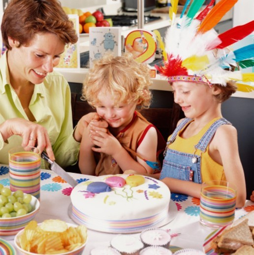 Mother with children (2-5) cutting birthday cake, smiling : Stock Photo