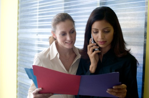 Stock Photo: 1672R-14280 Two businesswomen in office, one using mobile phone