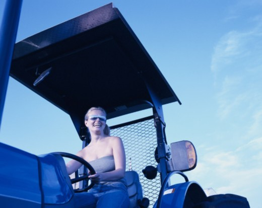 Woman driving tractor : Stock Photo