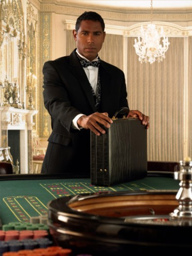 Man standing with briefcase at roulette table, portrait : Stock Photo
