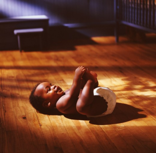 Stock Photo: 1672R-14808 Baby boy (9-12 months) lying on floor, playing with feet