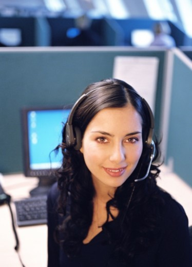 Young woman in call centre, wearing headset, smiling, portrait : Stock Photo