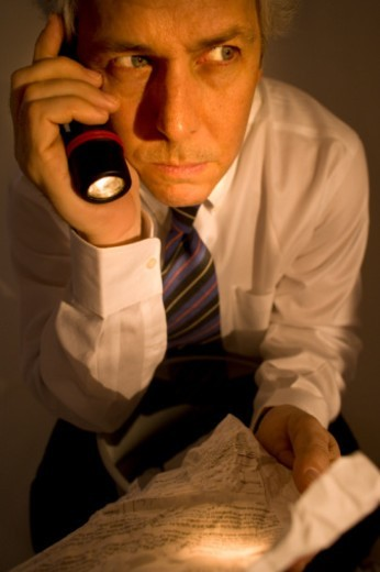 Stock Photo: 1672R-15431 Mature man holding crumpled paper, gripping flashlight
