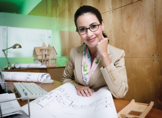 Architect at desk with blueprints, portrait : Stock Photo