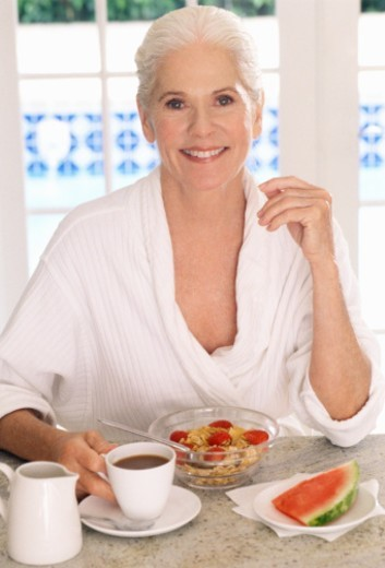 Stock Photo: 1672R-1626 Mature woman having breakfast, smiling, portrait, close-up