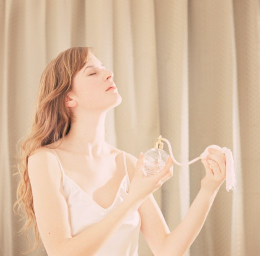 Stock Photo: 1672R-16445 Young woman spraying perfume, side view