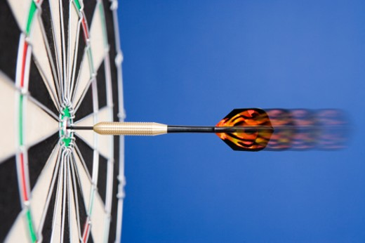 Dartboard, with dart in bull's eye, close-up, (blurred motion) : Stock Photo