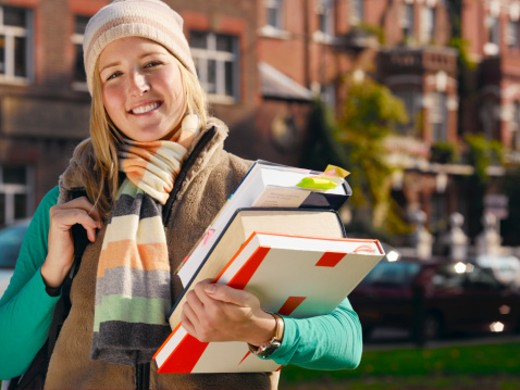 Young woman carrying pile of books, smiling, portrait : Stock Photo