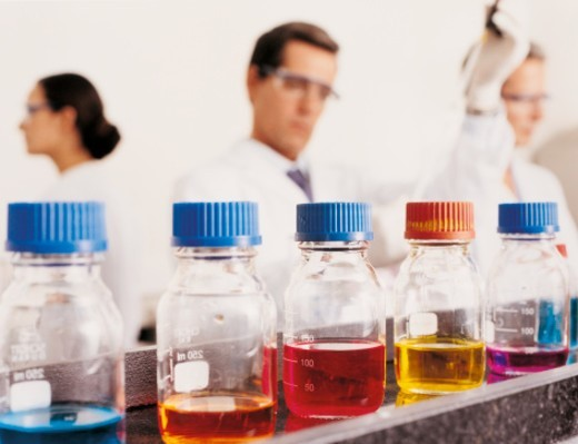 Jars in laboratory, three scientists working in background : Stock Photo