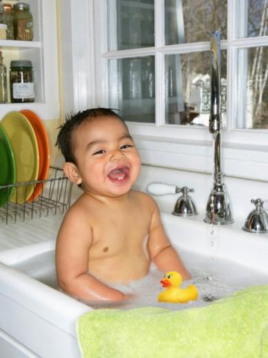 Baby boy (9-12 months) bathing in kitchen sink, smiling, portrait : Stock Photo