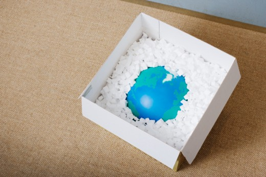 Globe in open cardboard box surrounded with pieces of foam, elevated view, close-up : Stock Photo