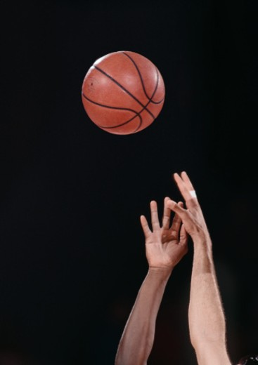 Two men reaching for basketball, close-up of hands : Stock Photo