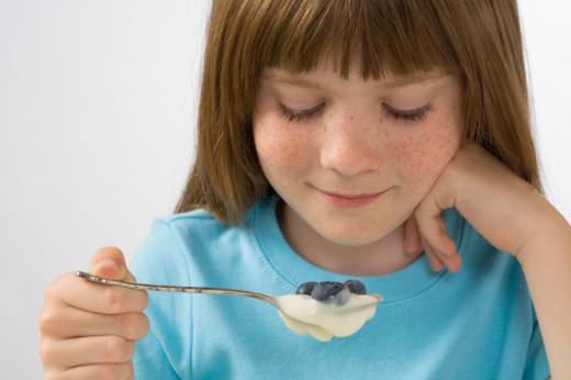 Stock Photo: 1672R-18080 Girl (9-11) eating yoghurt and blueberries