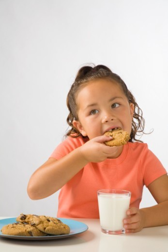 Young girl (4-6) eating plate of cookies : Stock Photo
