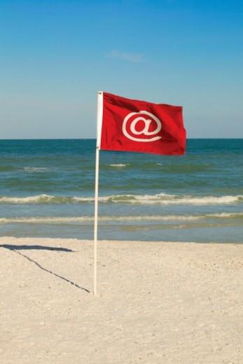 Flag with '@' symbol on beach : Stock Photo