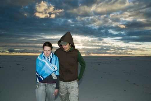 Young couple walking on beach, dusk : Stock Photo