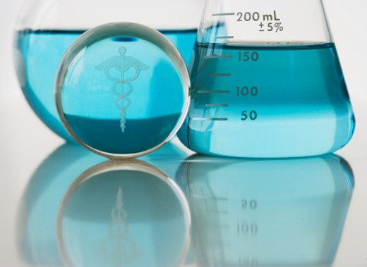 Cadeuseus with laboratory beakers filled with liquid, close-up : Stock Photo
