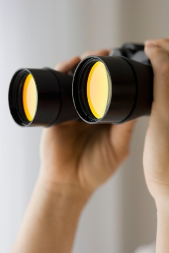 Stock Photo: 1672R-20027 Mature man holding binoculars, close-up of hands