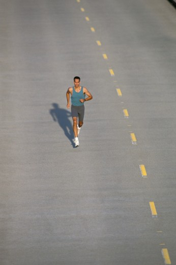 Stock Photo: 1672R-20251 Man jogging on street, elevated view