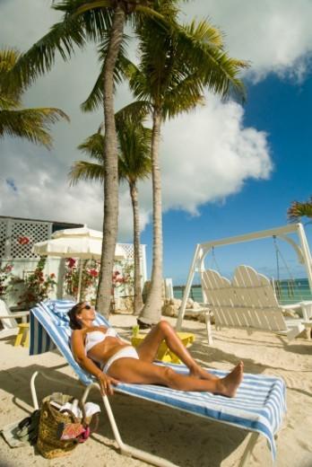 USA, Florida, Florida Keys, young woman sunbathing on beach : Stock Photo