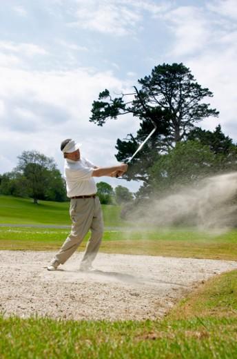 Senior man playing golf, standing in sand bunker, swinging : Stock Photo